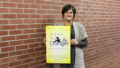 Teacher Samantha Sulek holds a large sign announcing her as a 2019-20 LifeChanger of the Year nominee.