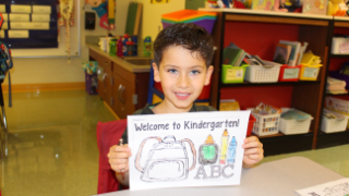 Boy holding Welcome to Kindergarten sign