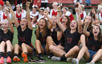Female athletes cheering at a pep rally