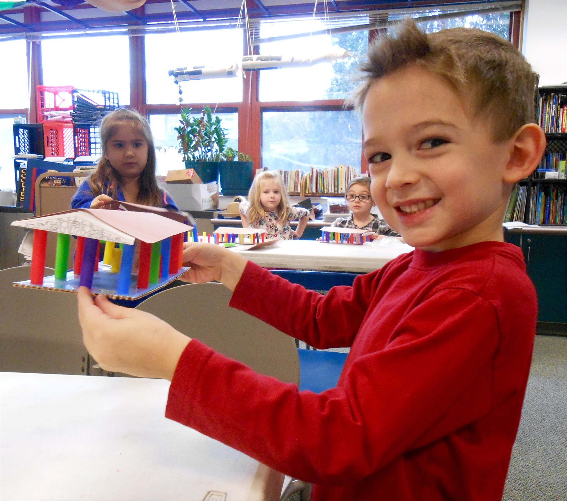 Kindergartener holds model of ancient building.