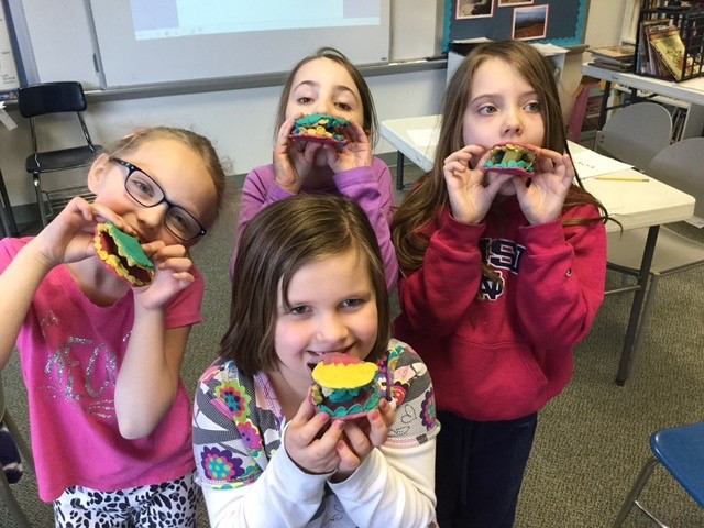Second graders display clay models of sets of teeth.