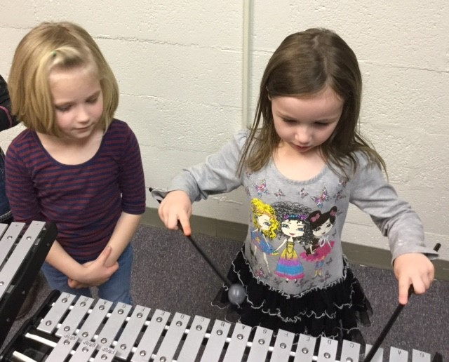 Kindergarteners explore musical instruments to make sound.