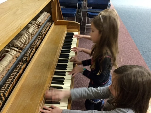 Kindergarteners explore musical instruments to make sound.