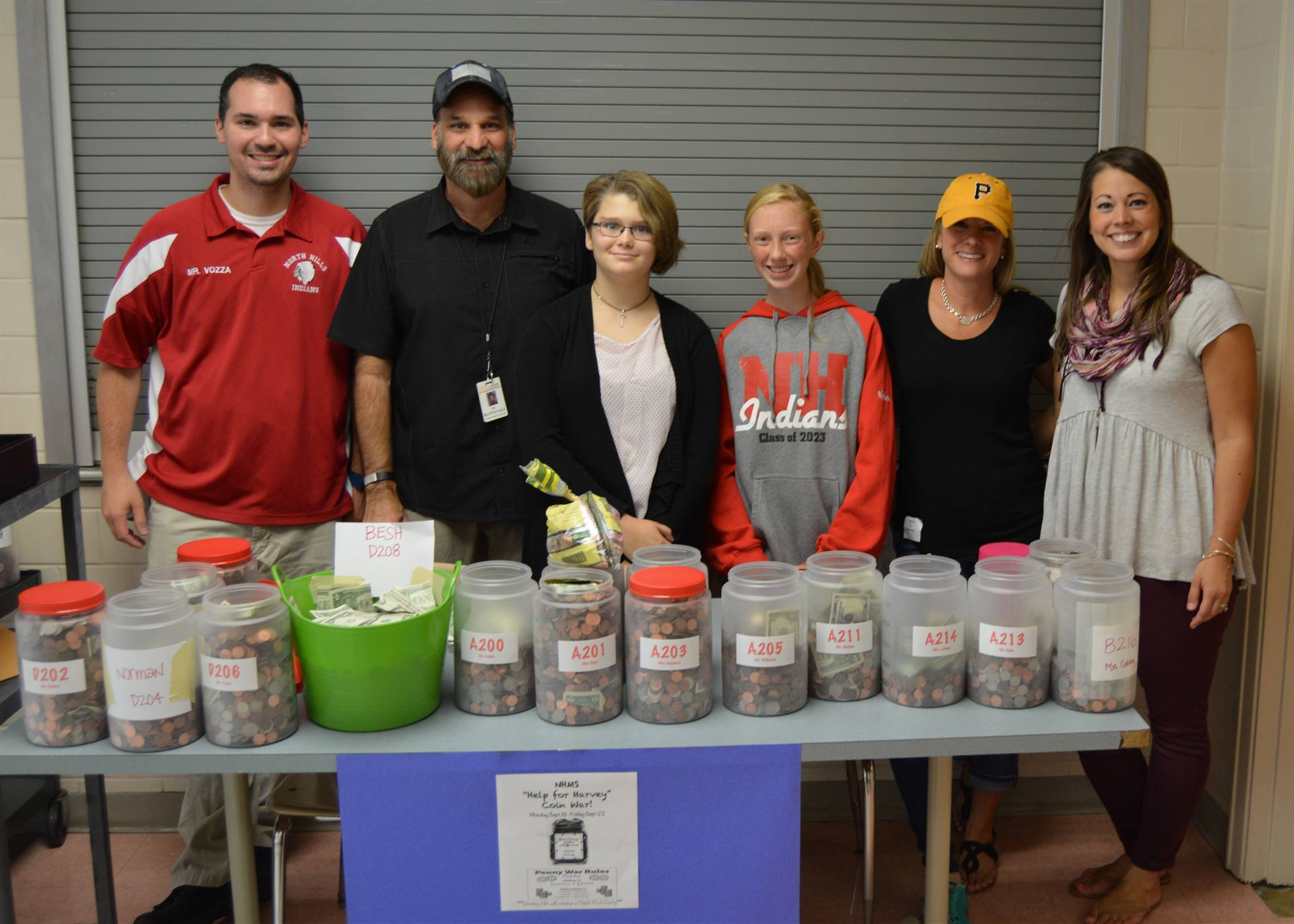 Photo of middle school students and staff with coin collected during a Coin War for Hurricane Harvey