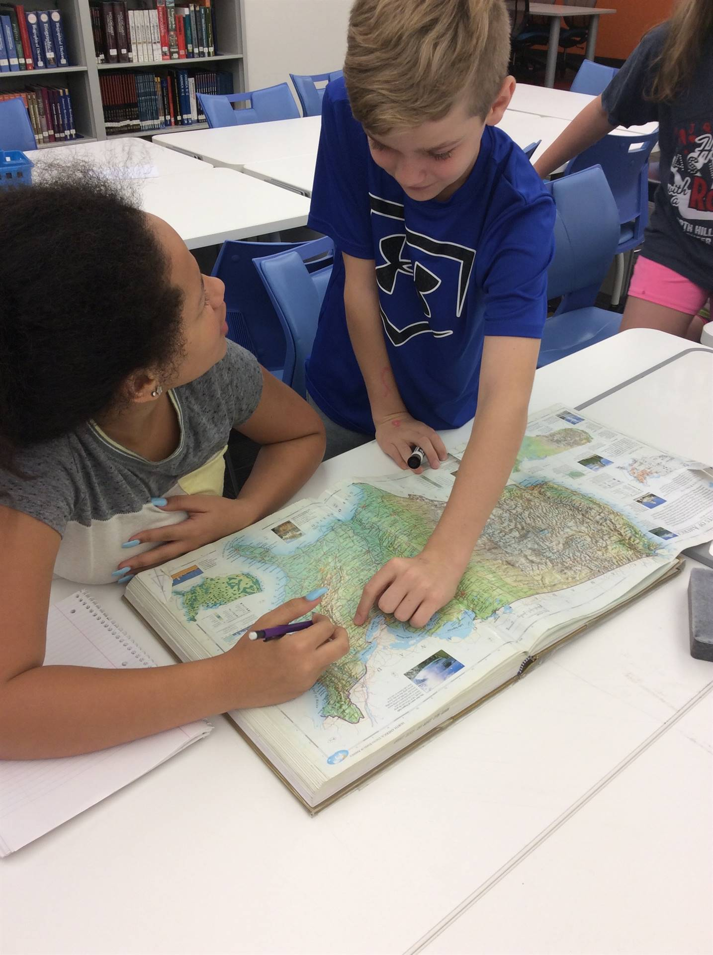 Students use an atlas.
