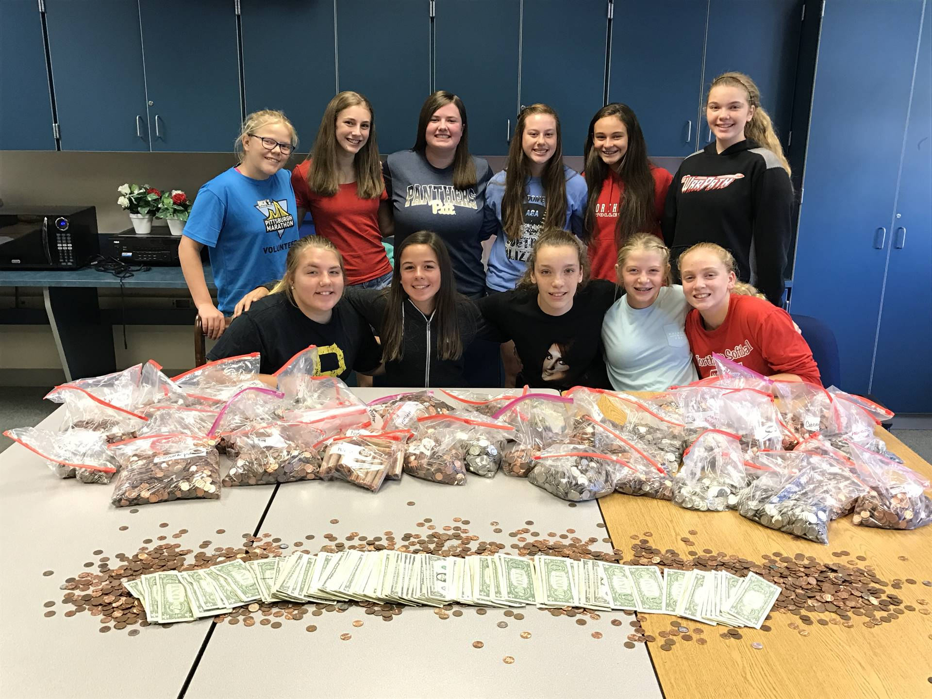 Photo of North Hills Middle School students posing with Coin War monies raised for Hurricane Harvey