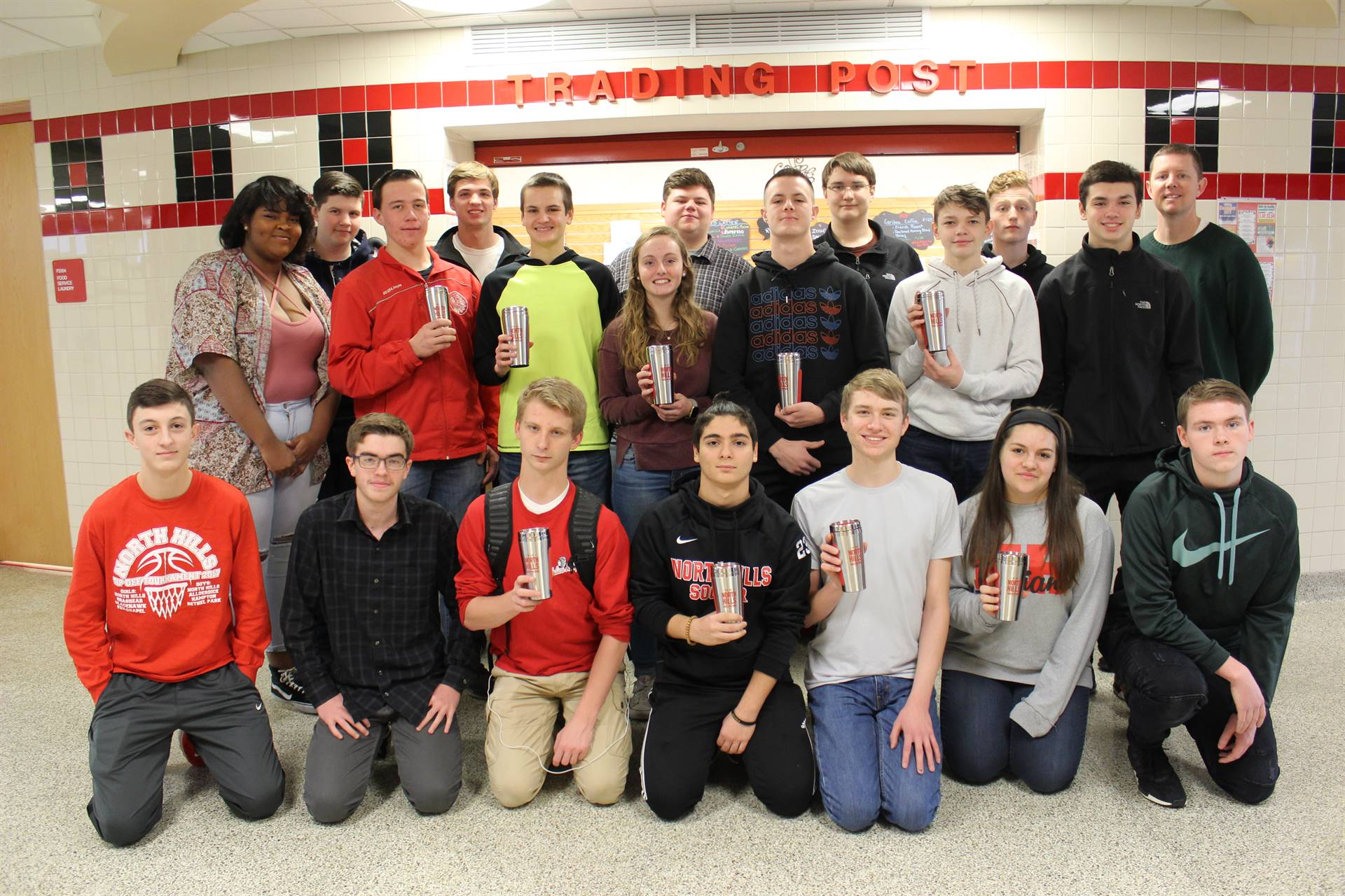 "High School Business Ownership students pose with the reusable ""We Are North Hills"" coffee tumbler."
