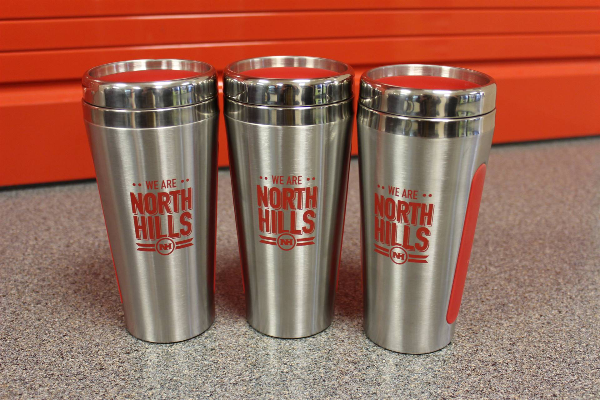 "Stainless steel, 15 ounce ""We Are North Hills"" reusable tumbler with red accents"