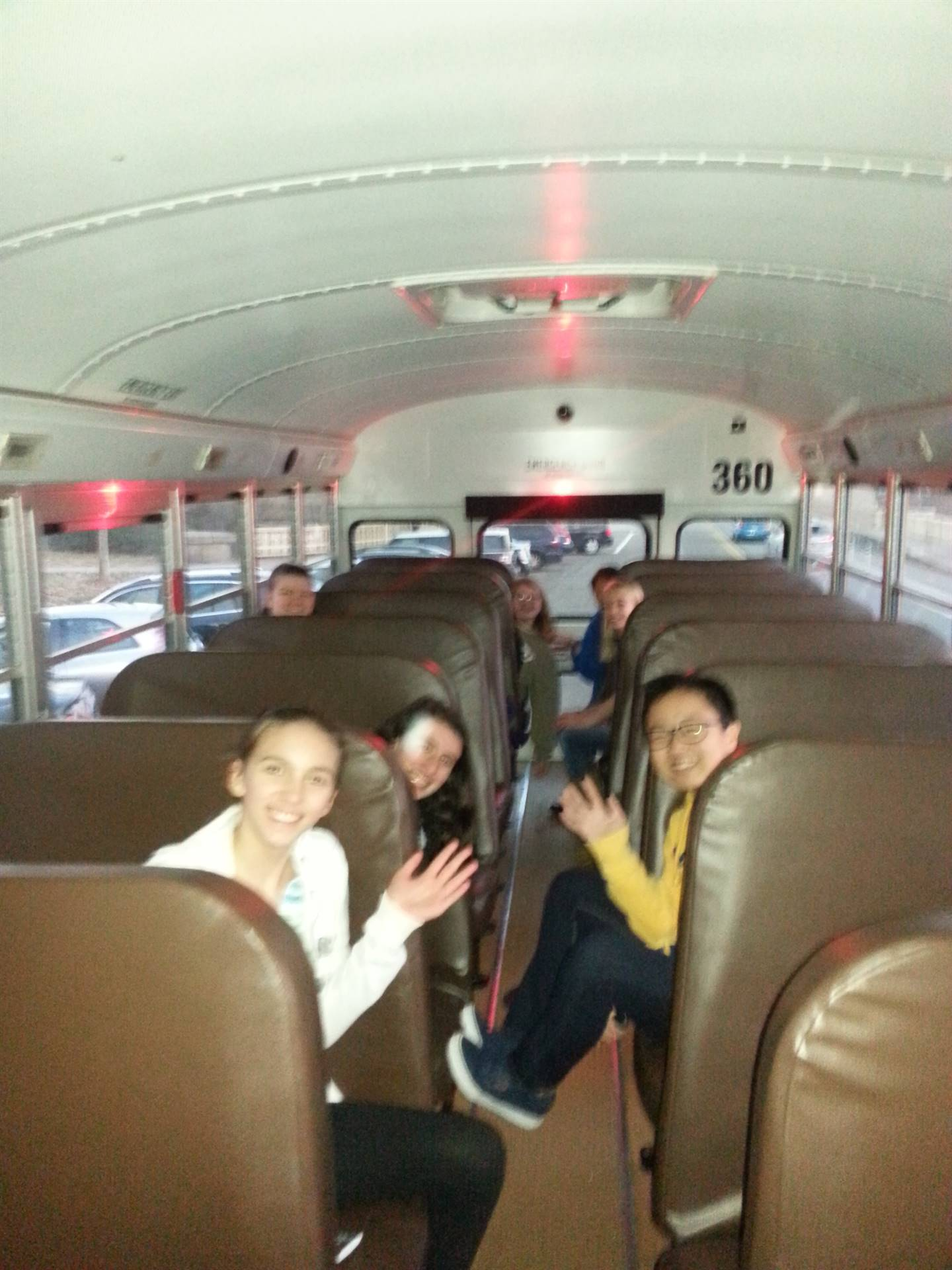 Students wave on a bus.