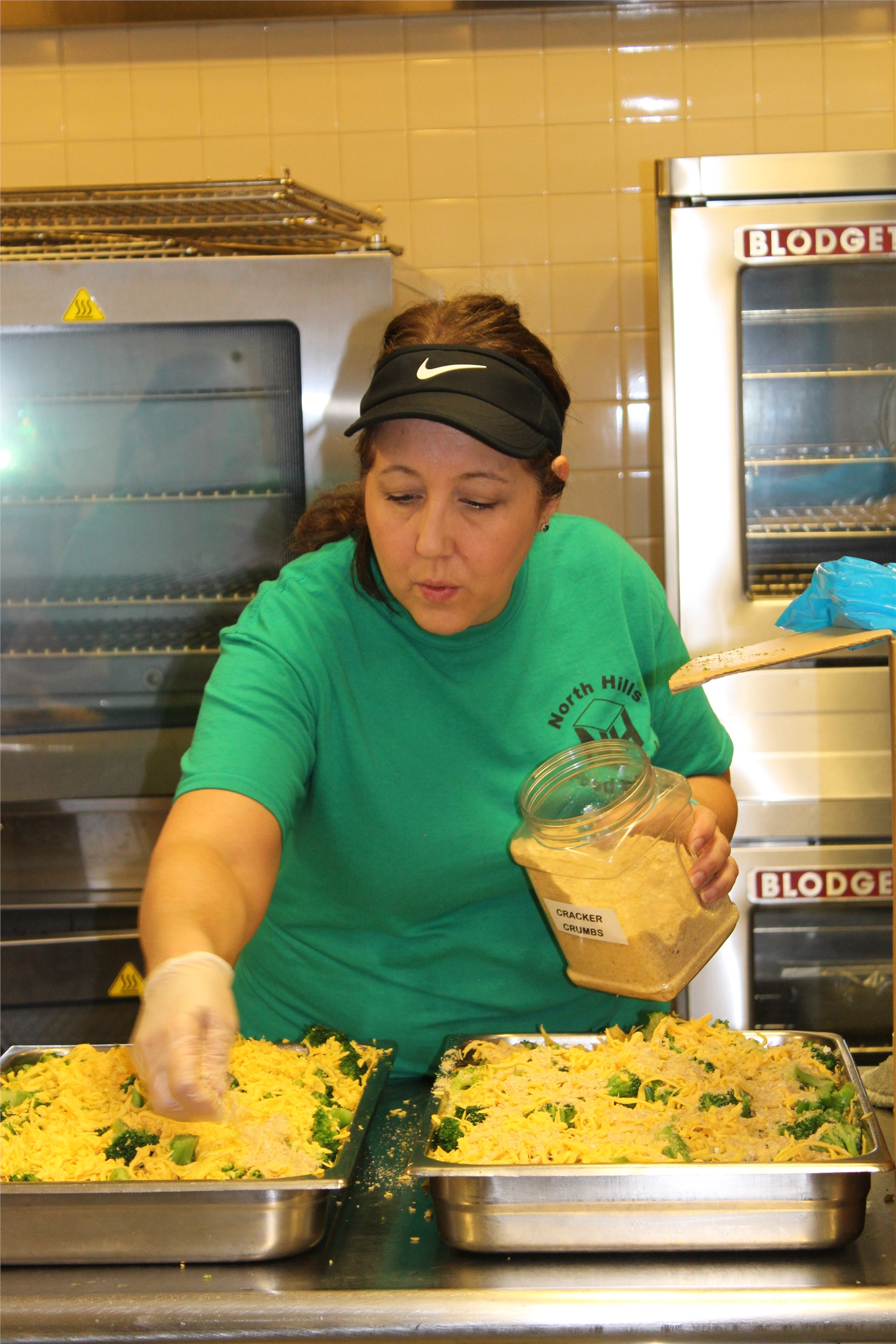Food Service Employee Makes Broccoli and Cheese Dish for Student Lunch