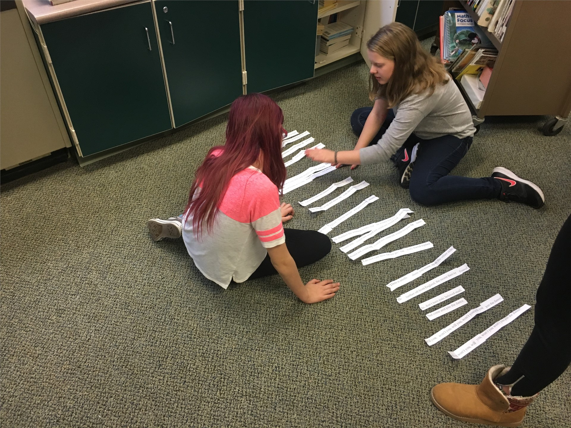 Students portion off poem lines from one long ticker strip.