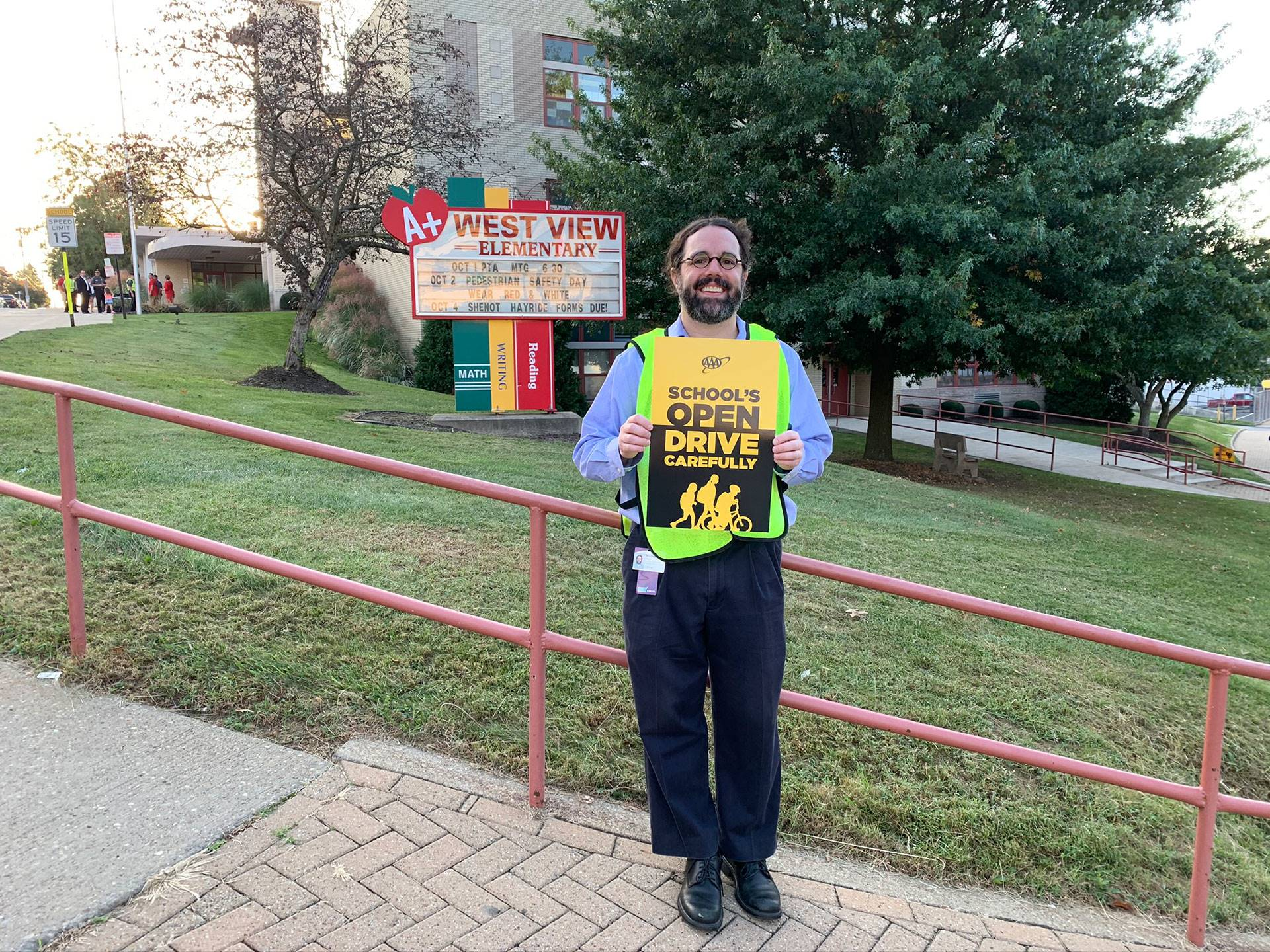 "Man holds ""Schools Open Drive Carefully"" sign  for International Walk to School Day at West View Ele"
