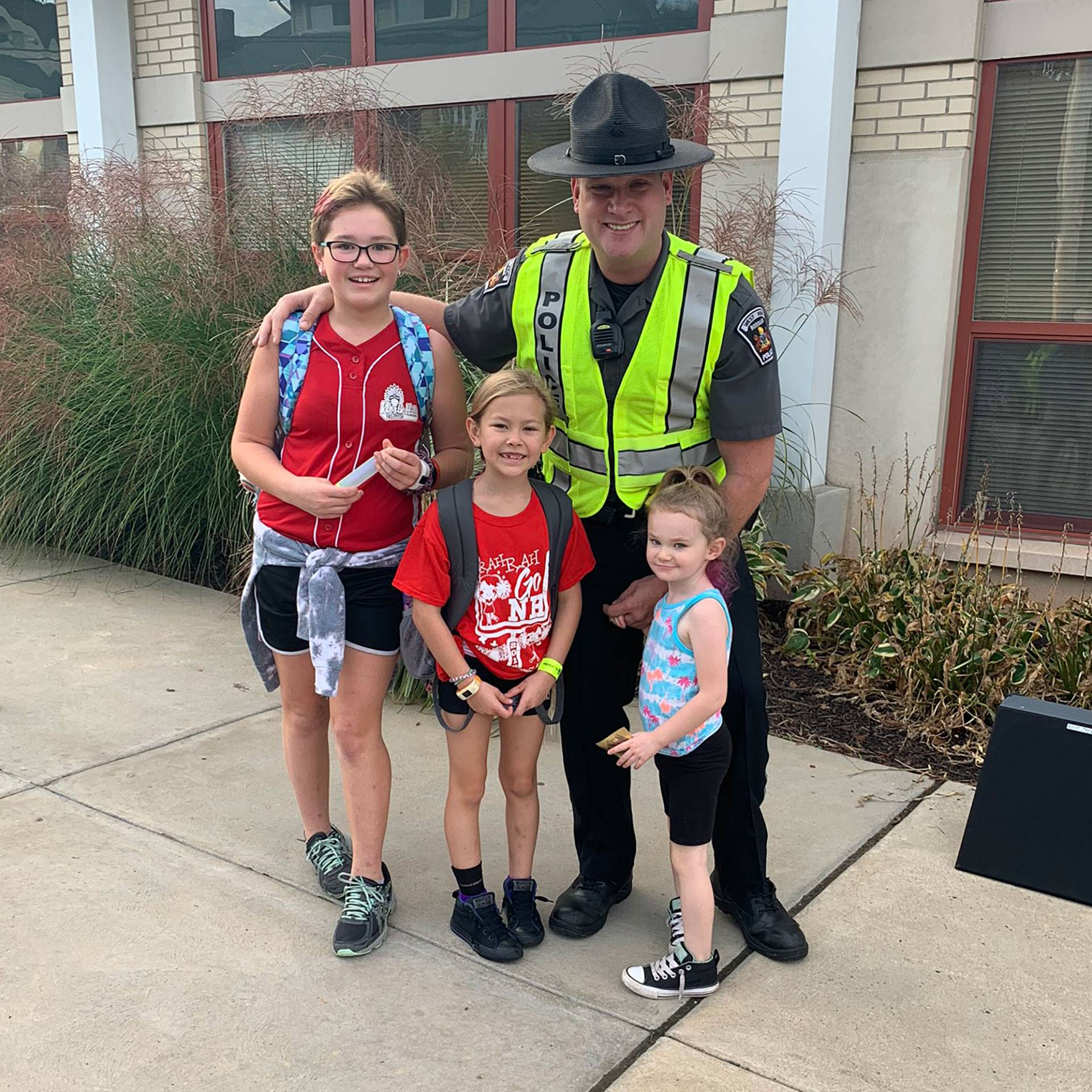 A West View police officer posing with his three daughters on International Walk to School Day on Oc