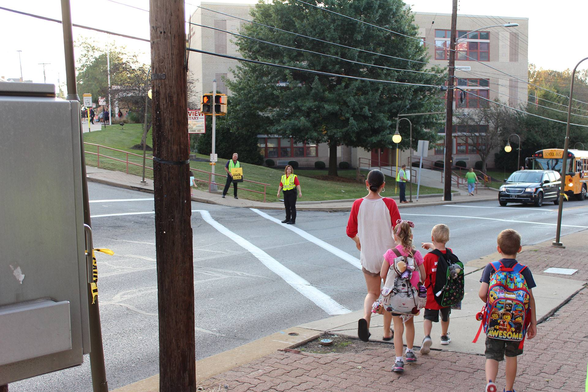 Crossing guards prepare to let a family cross the street at West View Elementary School