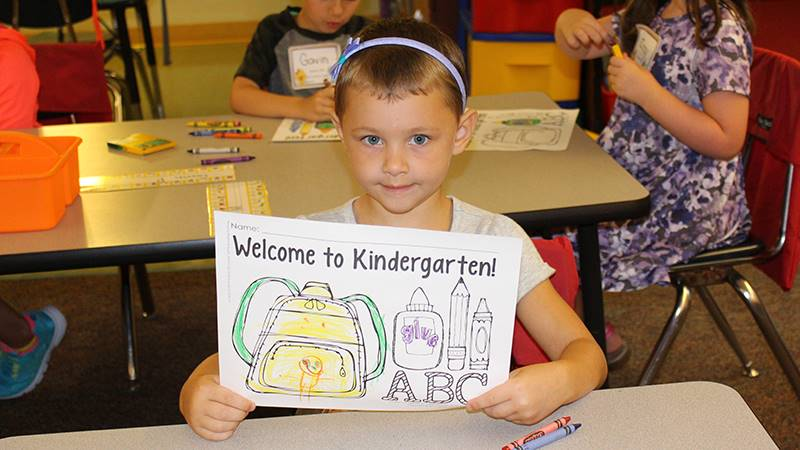 """Kindergartner on the first day of school holding """"Welcome to Kindergarten"""" picture"""