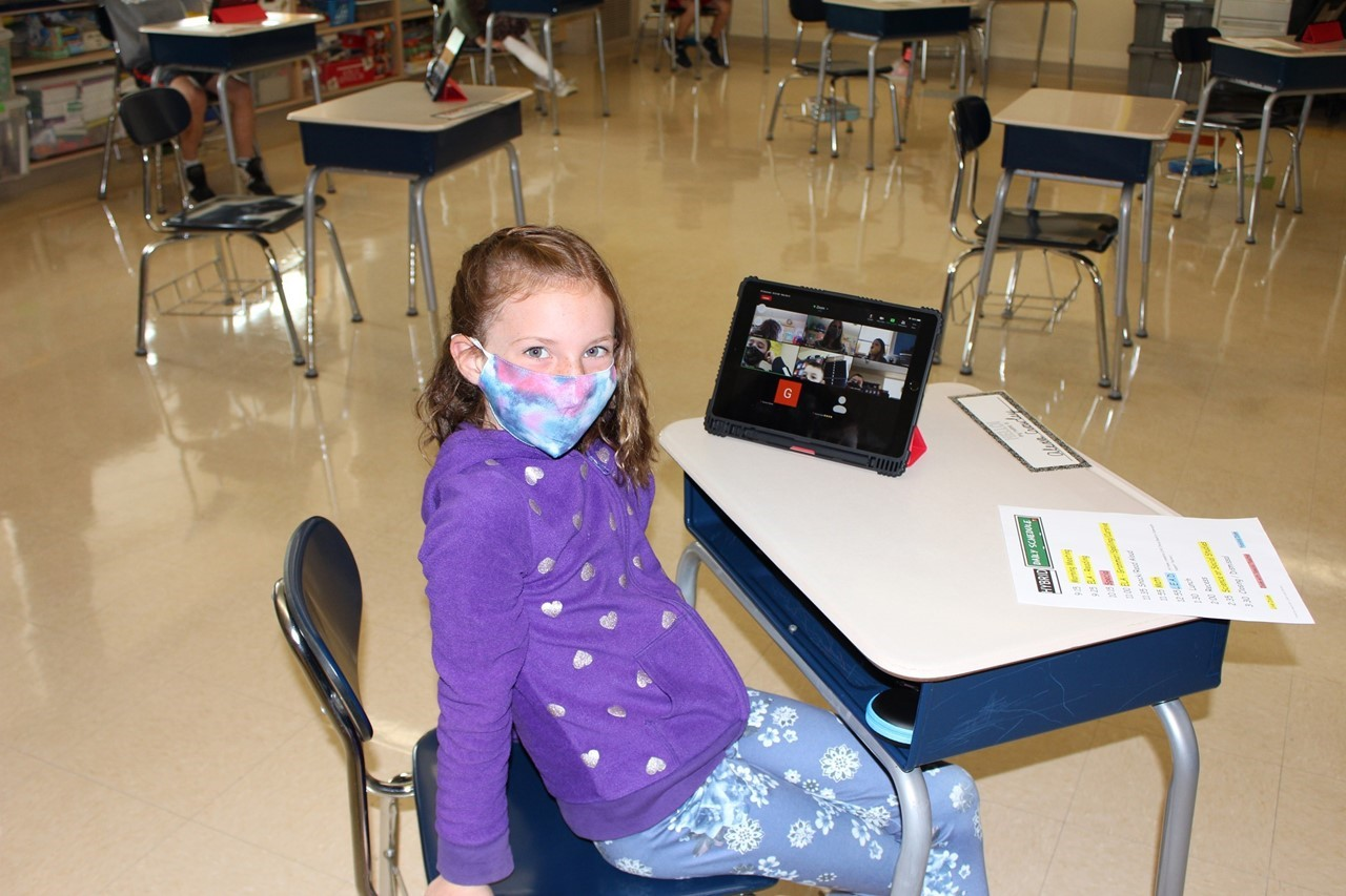 Female student in classroom with iPad showing students learning remotely on screen
