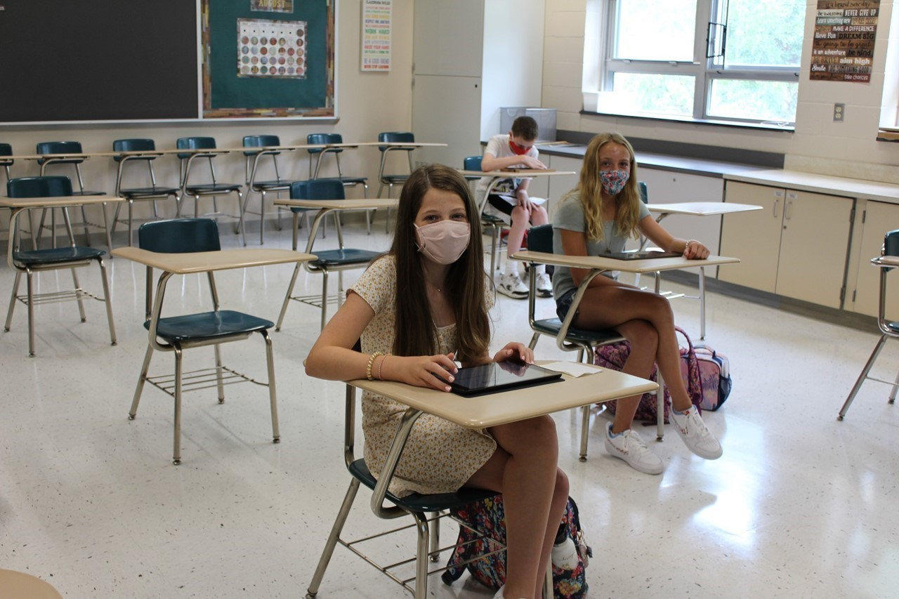 Students seated at desks in school wearing masks