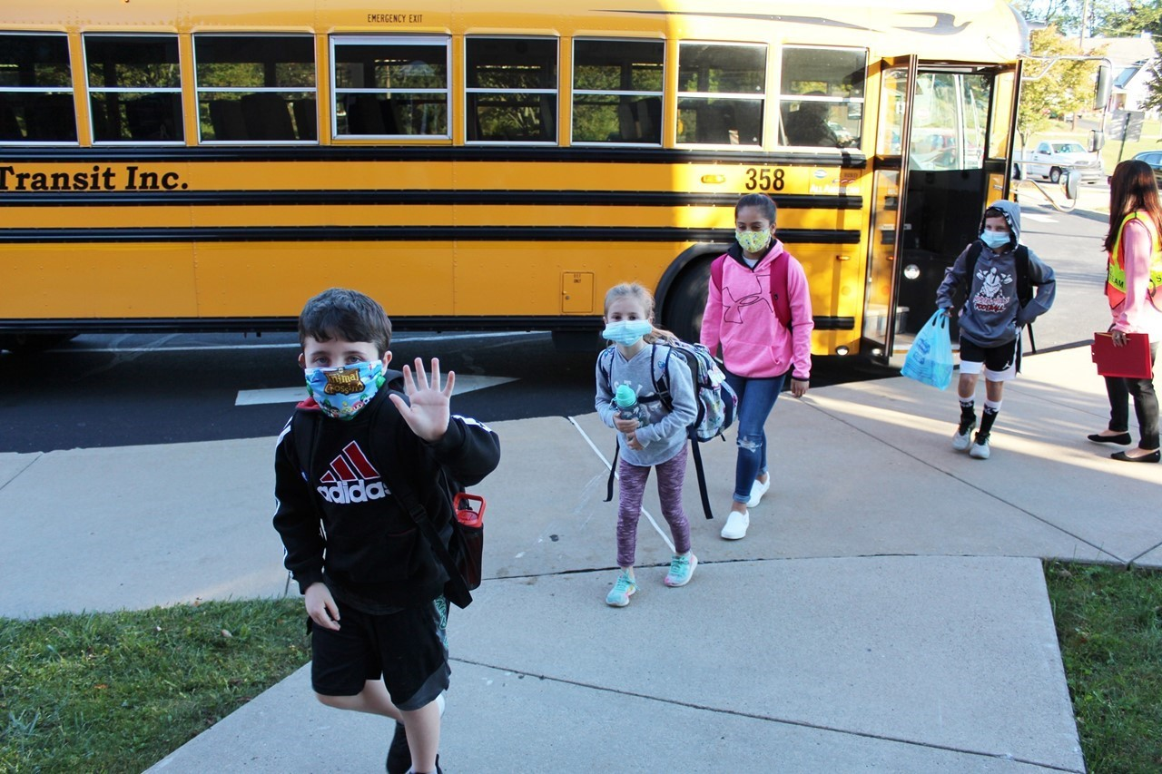 Students exiting bus and walking into school