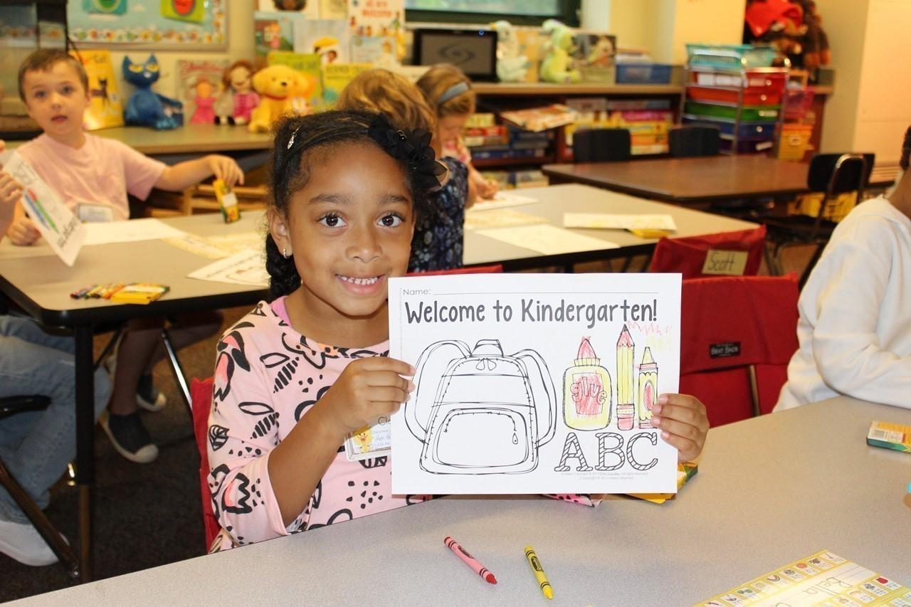 "Kindergarten student holding a ""Welcome to Kindergarten"" picture"