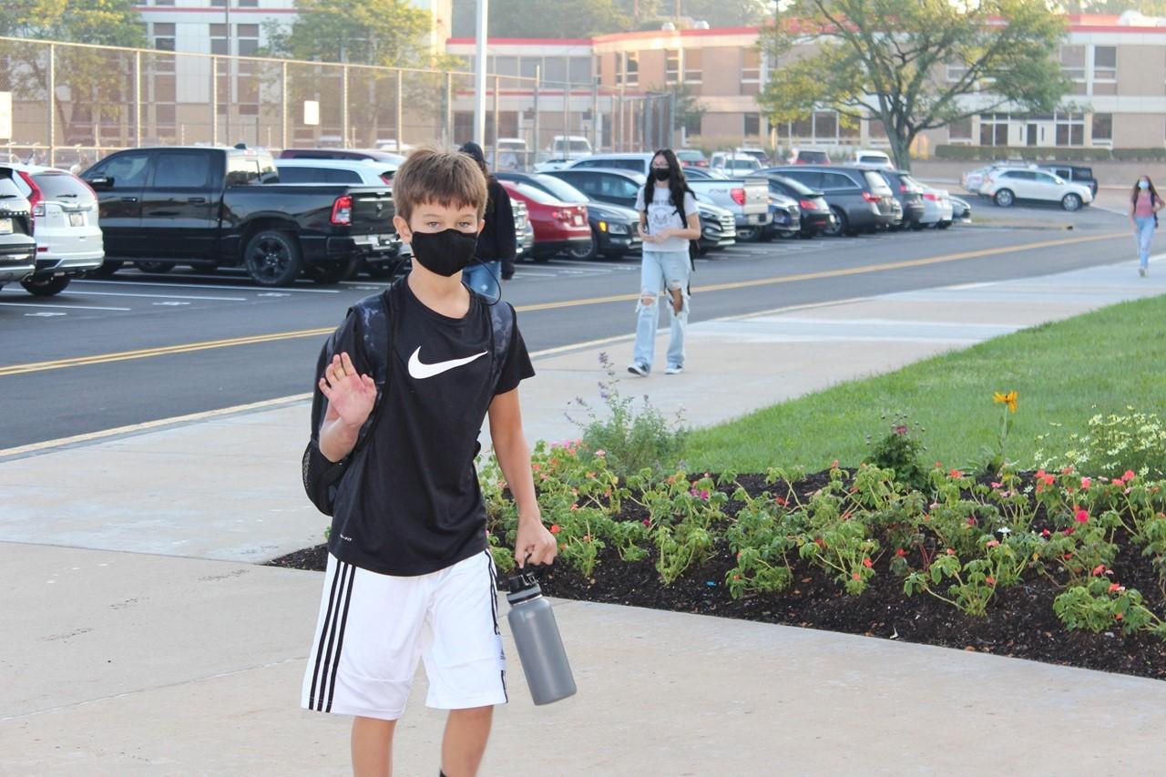 student walking into school waving