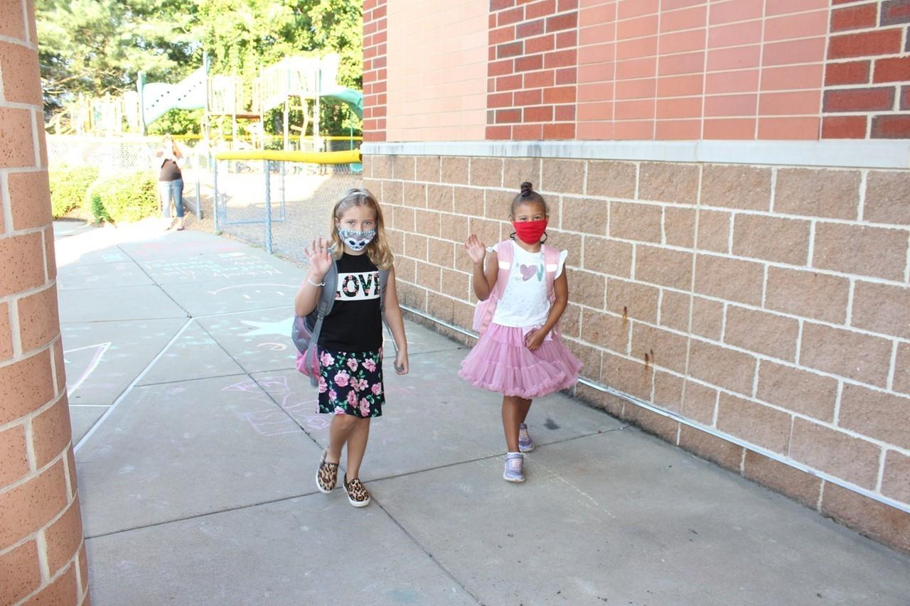 Two girls walking into school waving