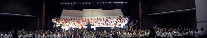 Large grouping of students singing in vocal concert